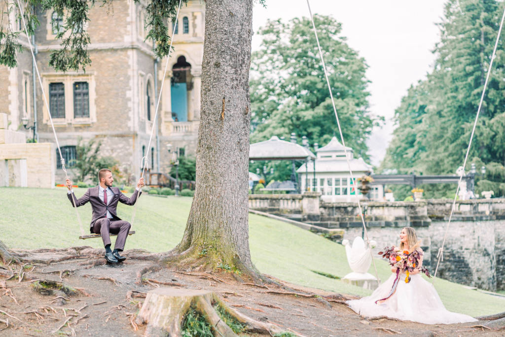 Bride and groom on swings at Cantacuzino Castle, Romania